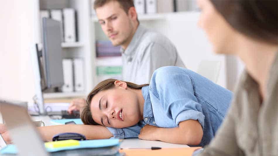 young woman sleeping with her head on office desk